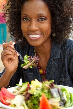happy African American woman eating salad