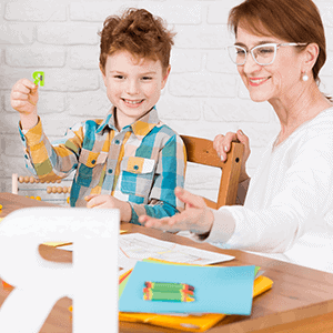 child working on letters with teacher
