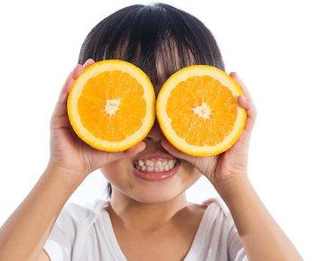 child using oranges as glasses