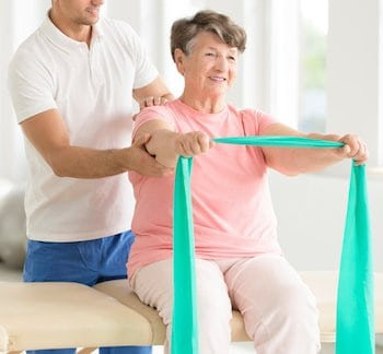 Elderly woman doing active pnf exercises with a teal scarf