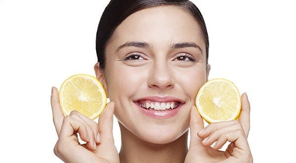 resh faced young female holding lemon slices and smiling..Light retouching, skin texture intact!""