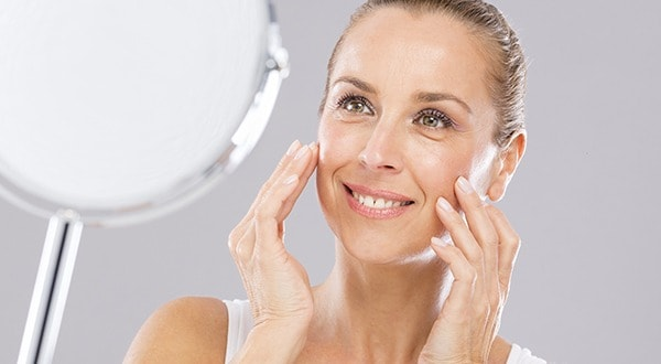 Mature woman with tenderness skin looking to the mirror.