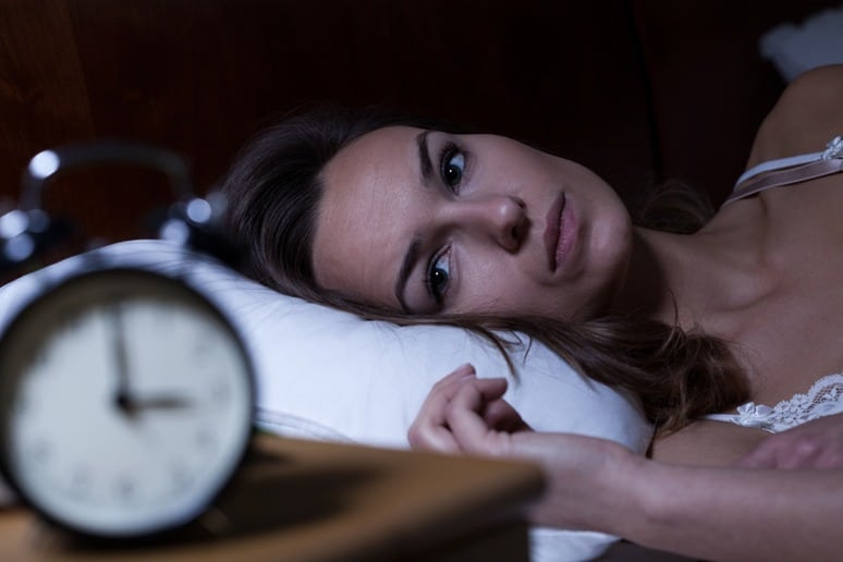 Woman Looks Frustrated at a Clock Due t Lack of Sleep
