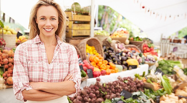 Woman Stands Smiling in Front of Fresh Organic Produce