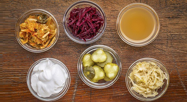 op view of glass bowls against wood: kimchi, red beets, apple cider vinegar, coconut milk yogurt, cucumber pickles, sauerkraut