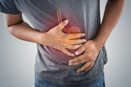 man with acid reflux gripping stomach
