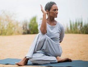 African American woman doing yoga stretch on mat