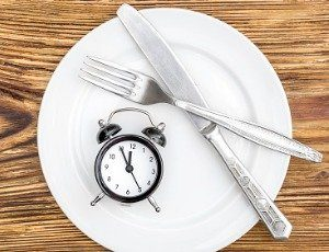 empty plate on table with knife, fork, and alarm clock