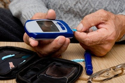 man checking blood sugar level with glucometer