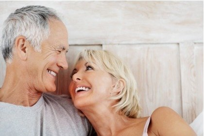 happy mature couple in bed looking at each other