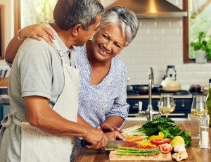 African American couple cooking healthy meal in kitchen