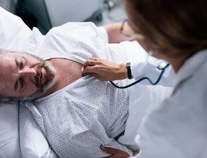 doctor checking heart rate of male patient in hospital bed