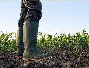 farmer standing in field in rubber boots