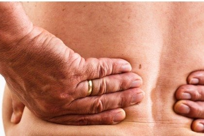 mature man with lower back pain holding back
