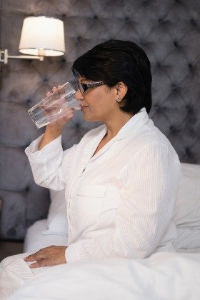 mature woman sitting on bed drinking a glass of water