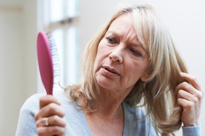 woman looking at hair brush concerned about hair loss
