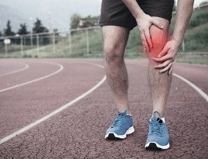 man holding painful knee on running track