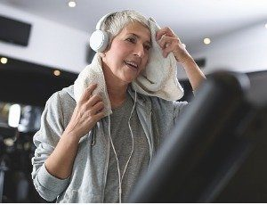 woman on exercise machine at gym wiping away perspiration with towel