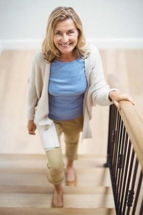 smiling woman walking up stairs