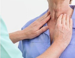 doctor examining woman's neck for goiter