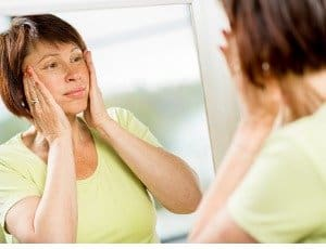 woman looking in mirror pulling back sagging skin