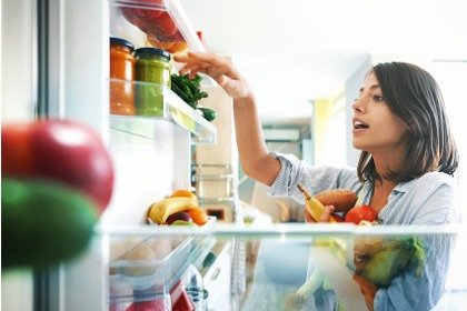 woman picking fruits and vegetables from fridge