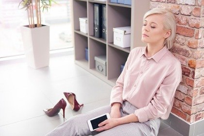 business woman sitting on floor with eyes closed taking a break