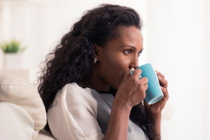 woman drinking from blue mug